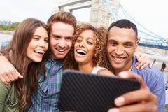 Grupp av vänner som tar Selfie vid tornbron i London royaltyfria bilder