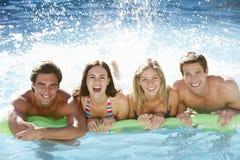 Grupp av vänner som tillsammans kopplar av i simbassäng Royaltyfri Fotografi