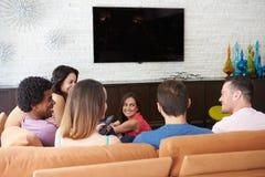 Grupp av vänner som tillsammans sitter på Sofa Watching TV royaltyfria foton