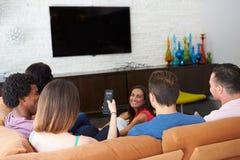 Grupp av vänner som tillsammans sitter på Sofa Watching TV royaltyfria bilder