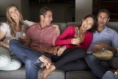 Grupp av vänner som tillsammans sitter på Sofa Watching TV arkivbilder