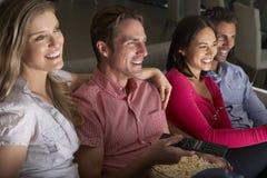 Grupp av vänner som tillsammans sitter på Sofa Watching TV arkivfoton