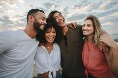 Grupp av vänner som tillsammans står på stranden och skratta royaltyfria bilder