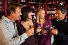 Grupp av vänner som tillsammans tycker om drinken i stång Arkivbild