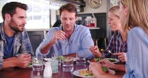 Grupp av vänner som tillsammans tycker om mål i restaurang stock video