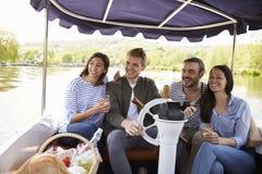 Grupp av vänner som tycker om dag ut i fartyg på floden tillsammans Arkivbilder