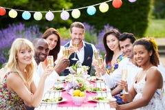 Grupp av vänner som tycker om det utomhus- matställepartiet Arkivfoto