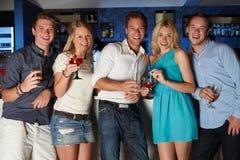 Grupp av vänner som tycker om drinken i stång arkivbild