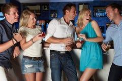 Grupp av vänner som tycker om drinken i stång arkivbilder