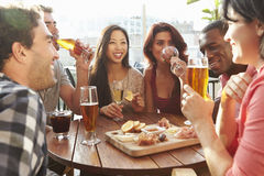 Grupp av vänner som tycker om drinken och mellanmålet i takstång arkivbild