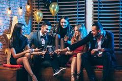 Grupp av vänner som tycker om hällande champagne för parti och har gyckel arkivfoton