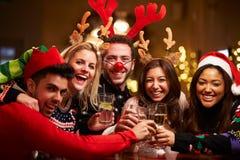 Grupp av vänner som tycker om juldrinkar i stång Fotografering för Bildbyråer