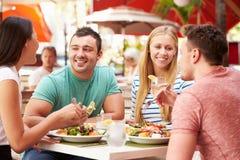 Grupp av vänner som tycker om lunch i utomhus- restaurang Royaltyfria Foton