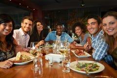 Grupp av vänner som tycker om mål i restaurang Fotografering för Bildbyråer