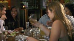 Grupp av vänner som tycker om mål i restaurang stock video