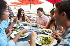 Grupp av vänner som tycker om mål på den utomhus- restaurangen Royaltyfri Fotografi