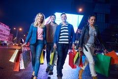 Grupp av vänner som tycker om som shoppar fotografering för bildbyråer