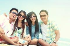 Grupp av vänner som tycker om strandferie arkivbild