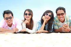 Grupp av vänner som tycker om strandferie arkivfoto