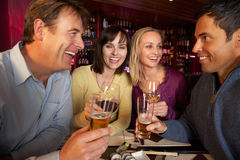 Grupp av vänner som tycker om Sushi i restaurang Arkivfoto