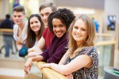 Grupp av vänner som ut hänger i shoppinggalleria Arkivfoto