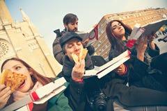 Grupp av vänner som utomhus äter pizza Royaltyfri Bild