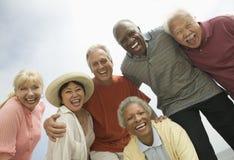 Grupp av vänner som utomhus skrattar (sikten för den låga vinkeln) royaltyfri foto