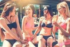 Grupp av vänner tillsammans i simbassängfritiden royaltyfria bilder