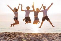 Grupp av vänner tillsammans på stranden som har gyckel lyckliga ungdomarsom hoppar på stranden Grupp av vänner som tycker om arkivfoton
