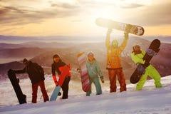 Grupp av vänsnowboarders som har gyckel på överkanten av berget arkivfoton