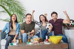 Grupp av vänsportfans som håller ögonen på att ropa för fotbollsmatch som är gladlynt royaltyfri foto