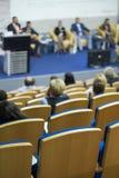 Grupp av värdar som sitter på etapp på tabellen under en konferens Fotografering för Bildbyråer