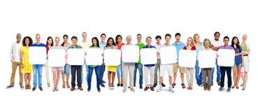 Grupp av världsfolk som rymmer 11 tomma plakat Arkivbilder