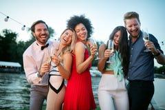 Grupp av v?nner som har gyckel och firar gruppsammankomsten royaltyfria bilder