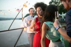 Grupp av v?nner som har gyckel och firar gruppsammankomsten royaltyfri fotografi