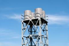 Grupp av vattentornet som stiger från träd mot blå himmel som konstrueras på en höjd som är tillräcklig att tryck ett vattenförsö royaltyfria bilder