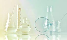 Grupp av vetenskaplig laboratoriumglasföremål med den klara vätskelösningen, forskning och utveckling arkivbild