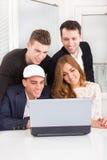 Grupp av vänner och kollegor som tillsammans ser bärbara datorn Arkivfoton