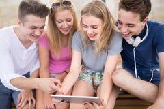 Grupp av vänner som använder den digitala minnestavlan Fotografering för Bildbyråer