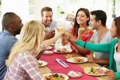 Grupp av vänner som gör rostat bröd runt om tabellen på matställepartiet Arkivbild