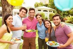 Grupp av vänner som har partiet i trädgård hemma Arkivfoton