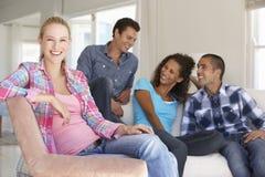 Grupp av vänner som kopplar av på Sofa At Home Together Royaltyfri Fotografi