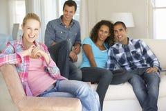 Grupp av vänner som kopplar av på Sofa At Home Together Royaltyfri Bild