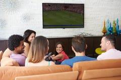 Grupp av vänner som sitter på Sofa Watching Soccer Together Royaltyfri Foto