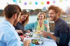 Grupp av vänner som äter mål på takterrass Arkivbild