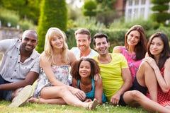 Grupp av vänner som tillsammans sitter på gräs Arkivbild
