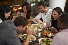 Grupp av vänner som tycker om aftonmål i restaurang Royaltyfria Bilder
