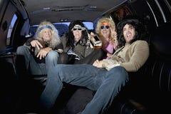 Grupp av vänner som tycker om alkohol i limousine Royaltyfri Foto