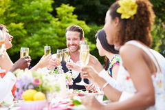 Grupp av vänner som tycker om det utomhus- matställepartiet Fotografering för Bildbyråer