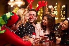 Grupp av vänner som tycker om juldrinkar i stång Royaltyfri Bild
